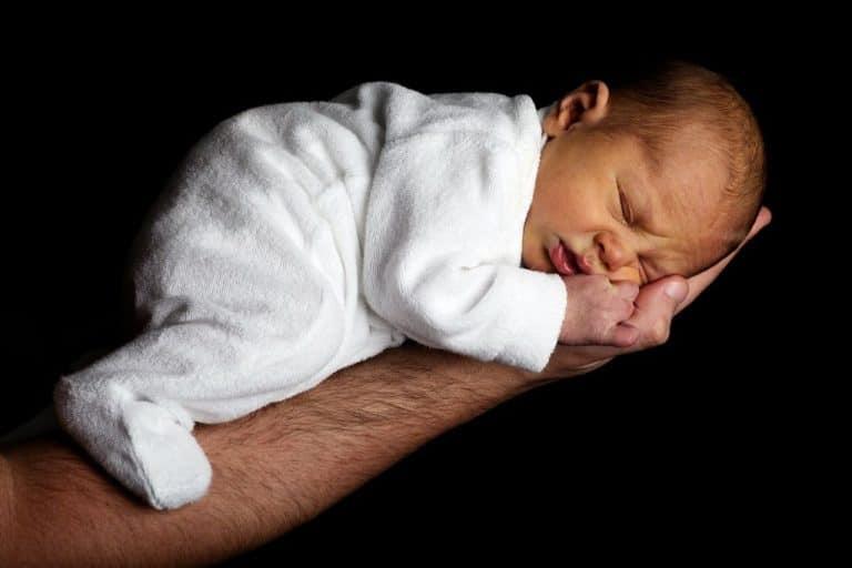 Baby slapend op vader hand